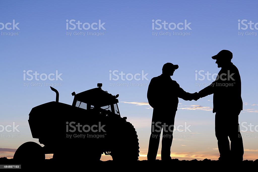 Farmers Handshake A royalty free image from the farming industry of two farmers shaking hands in front of a tractor. Agreement Stock Photo