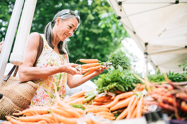 Farmers Market Shopping Mature Woman An older woman in her fifties shopping in a local farmers market with fresh, organic vegetables. She smiles as she chooses carrots. Horizontal image with copy space. farmer's market stock pictures, royalty-free photos & images