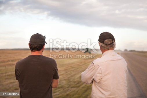 Two farmers watching combine combine harvester coming down canola field.