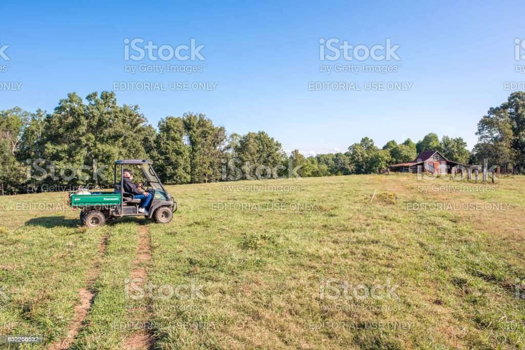 Farmers riding in a field in South Carolina Inman, South Carolina, Sept. 10, 2017: Farmers ride a motorized buggy all terrain vehicle, a Kawasaki Mule, over farmland in late summer, toward the barn to check on their pasture. 60-69 Years Stock Photo