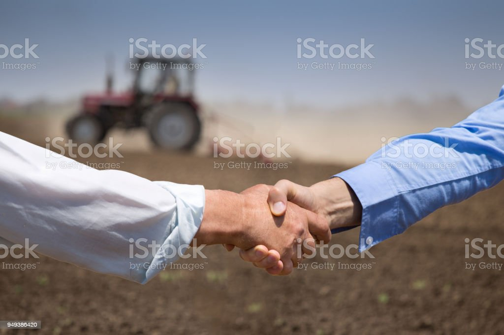 Landwirte, Händeschütteln vor der Traktor im Feld – Foto