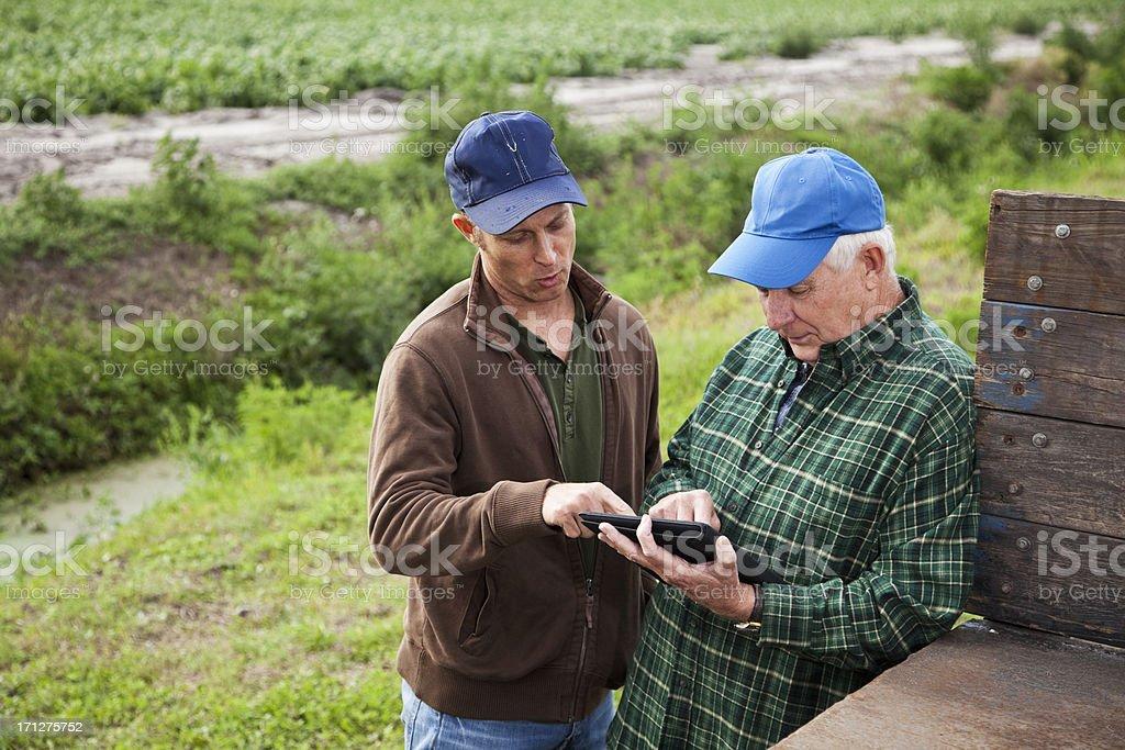 Farmers using digital tablet on potato farm stock photo