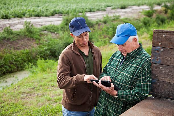 landwirte verwenden digitale tablet auf kartoffel-farm - alte wagen stock-fotos und bilder