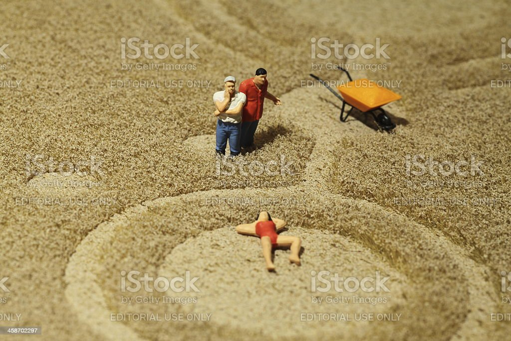 Farmers watching woman sunbathing in crop circle stock photo