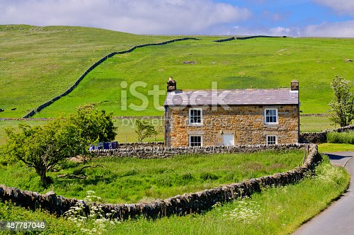 Cumbria, United Kingdom - June 23, 2015: Farmhouse amid Hills and Meadows in English countryside, Hadrian Wall area, United Kingdom. Trees and green grass are in foreground. Sky with clouds is in background. HDR photorealistic image.