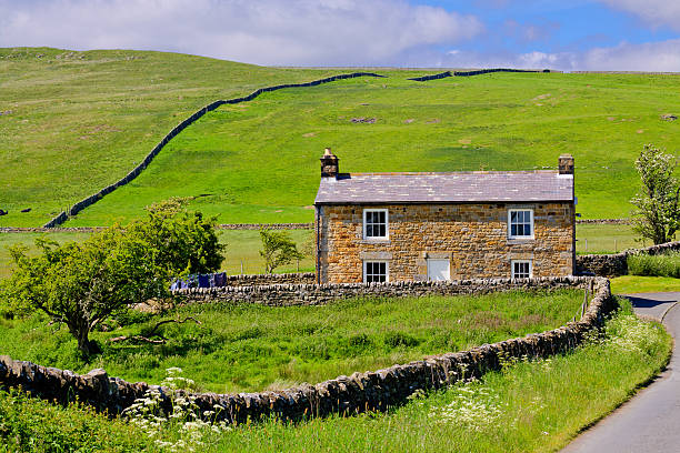 Farmhouse amid Hills and Meadows, Cumbria, England. Cumbria, United Kingdom - June 23, 2015: Farmhouse amid Hills and Meadows in English countryside, Hadrian Wall area, United Kingdom. Trees and green grass are in foreground. Sky with clouds is in background. HDR photorealistic image. amid stock pictures, royalty-free photos & images