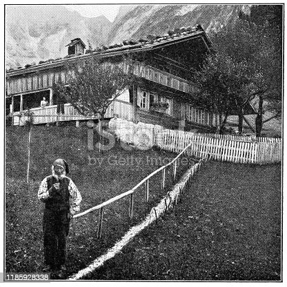 Farmer in front of a traditional farmhouse in rural Bern Canton, Switzerland. Vintage halftone photo circa late 19th century.