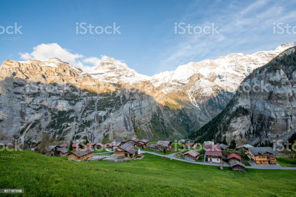 Farmhouse in village with swiss alps snow mountain in background in Grindelwald, Switzerland. Country village in Switzerland. stock photo