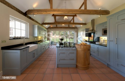a beautiful farmhouse kitchen in a fully restored and rebuilt farm. Old, weathered oak beams support the roof and ceiling. Brand new terracotta flooring compliments the pastel toned powder blue cupboards and large kitchen island. This is a modern featured kitchen with all the appliances but constructed in a traditional style and being faithful to the 500 year old building.