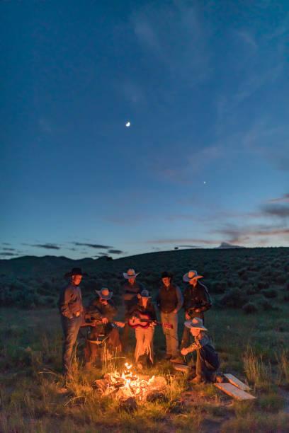 Farming Family Gathered Around a Campfire at Night stock photo