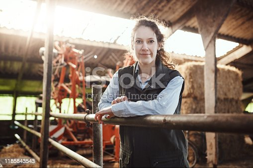 Shot of a confident young woman working at a dairy farm