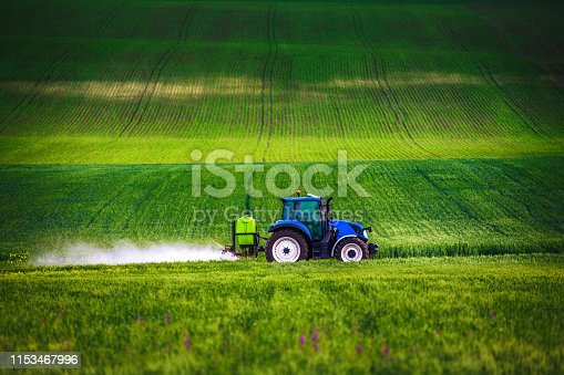 Farming tractor plowing and spraying on field.