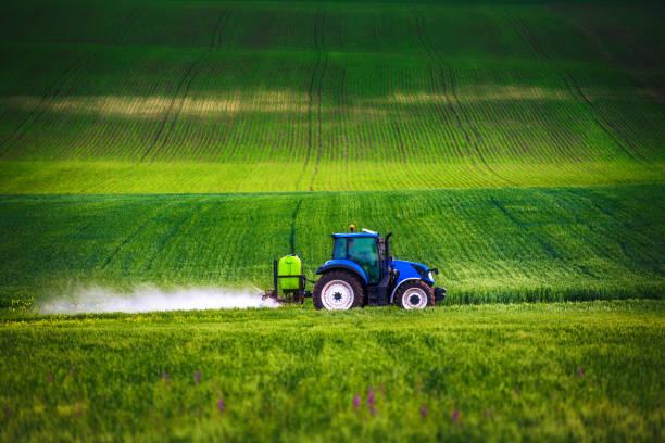 Landwirtschaftliche Traktoren pflügen und sprühen auf dem Feld – Foto