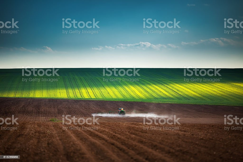 Farming tractor plowing and spraying on field stock photo