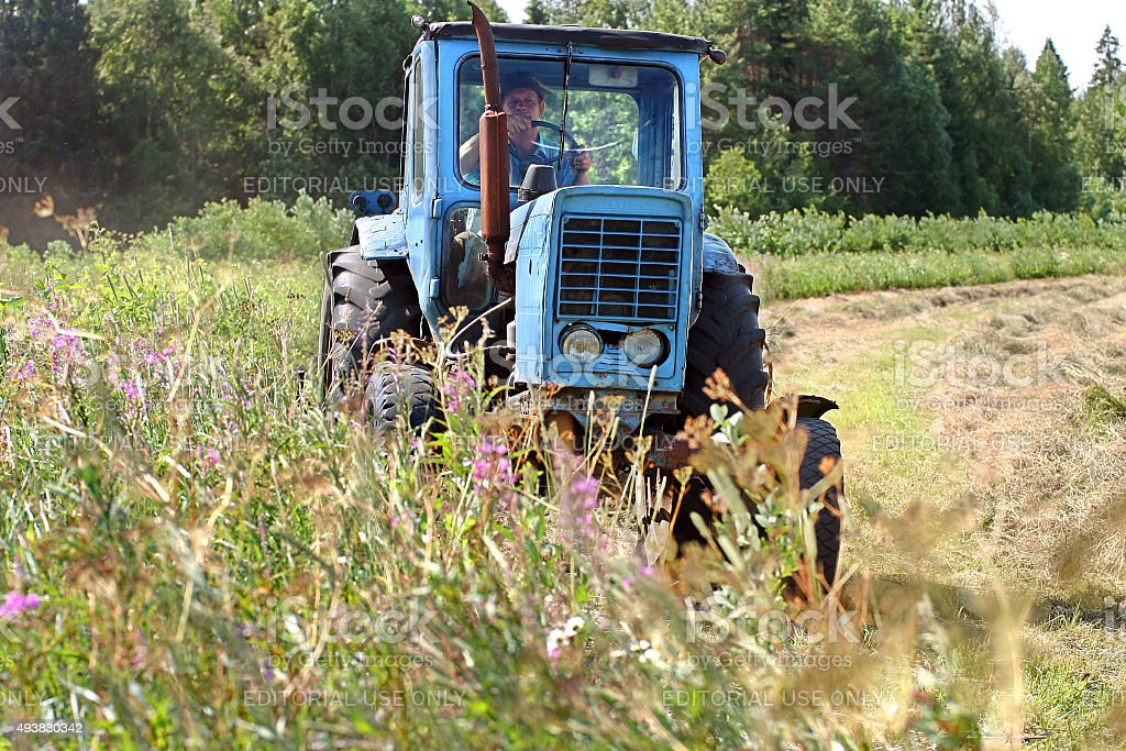 Farming tractor working in field of freshly cut during hayfield. stock photo