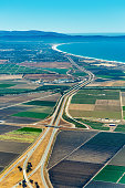 Pacific coast of California with farmland around freeway 101 and Monterey Bay visible in the up right corner. The picture was taken in the early July.