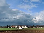Farmland and typical german small village under dramatic sky, january