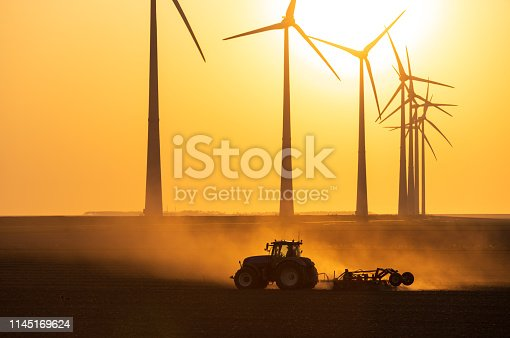 Tractor cultivating farmland during sunset at a row of windturbines producing sustainable energy. Groningen, Holland.