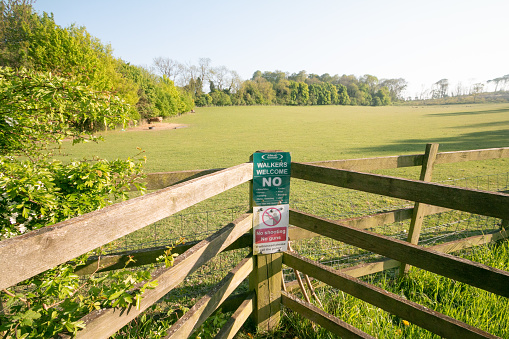 Farningham Wood Nature Reserve in Kent, England, with signs warning against shooting and welcoming walkers. It is part of Sevenoaks District Council.