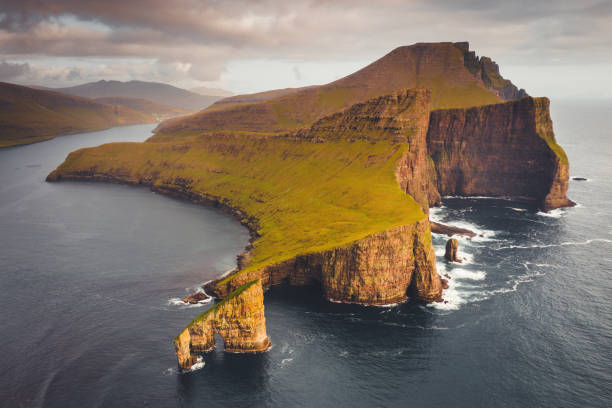 Faroe Islands Drangarnir Rocks Sunset Vagar Island Famous Drangarnir Rock Formation in the North Atlantic Ocean in warm golden sunset light. Aerial Drone Point of view of the iconic Drangarnir Rock Formation between the Islet Tindholmur and Vágar Island, Faroe Islands, Denmark, Nordic Countries, Europe rocky coastline stock pictures, royalty-free photos & images
