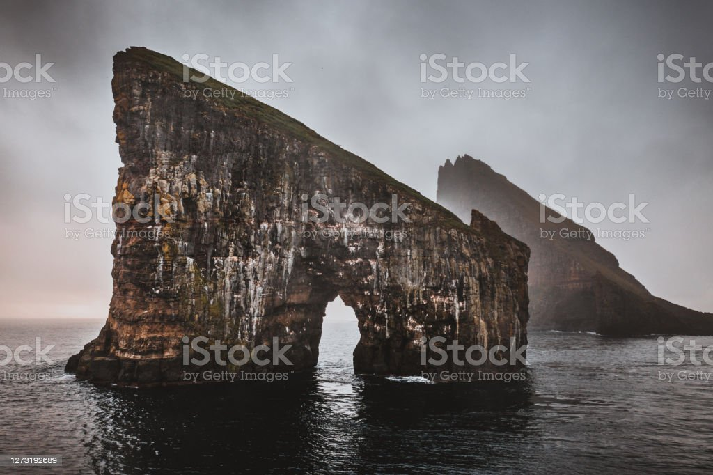 Faroe Islands Drangarnir Rocks Vagar Island Famous Drangarnir Rock Formation in the North Atlantic Ocean in moody fog sunset light. Between the Islet Tindholmur and Vágar Island, Faroe Islands, Denmark, Nordic Countries, Europe Atlantic Ocean Stock Photo