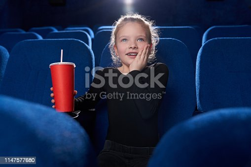 istock Fascinated girl watching movie in theatre. 1147577680