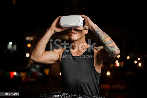 687096686 istock photo Fascinated muscular and tattooed man in night vision glasses 918609488