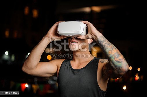 687096686 istock photo Fascinated muscular and tattooed young man in night vision glasses 918609346