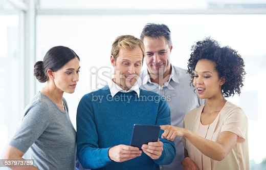 Shot of a group of colleagues using a digital tablet together