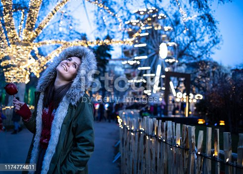 Beautiful woman walking by night on street, looking at christmas decoration.