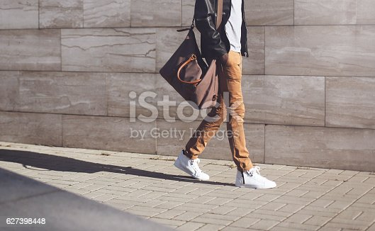 istock Fashion african man in black jacket walking in city 627398448