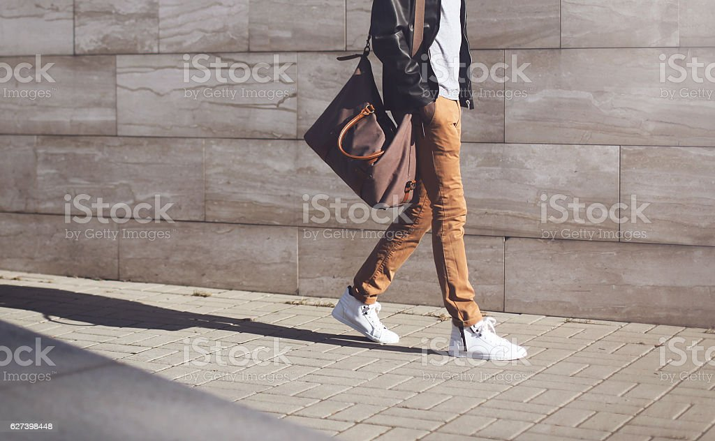 Fashion african man in black jacket walking in city stock photo