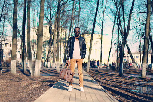 627398448 istock photo Fashion african man model wearing black leather jacket with bag 636345282