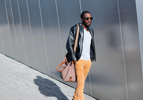 627398448 istock photo Fashion african man walks in evening city over urban background 602337804
