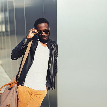 627398448 istock photo Fashion african man wearing sunglasses, black jacket in city 627398510