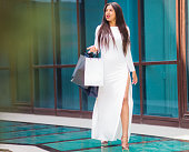 istock Fashion Afro woman in white beautiful dress holding many paper shopping bags while walking  at front of business building with blue windows. Shopaholic concept. 1170150585