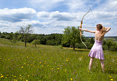 Young woman in pink dress is aiming on target on a beautiful spring meadow with flowers and trees.See some similar pictures from my portfolio: