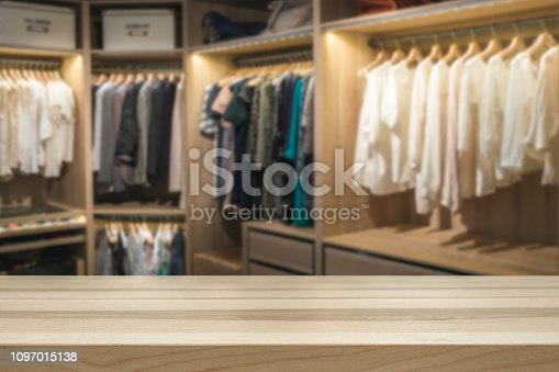 Empty table top for product display montage. Fashion and clothes concept. Walk in closet wardrobe blurred in the background.