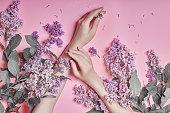 ファッション アート手自然化粧品女性、明るい紫色のライラックの花手に明るいコントラストのメイクアップで、ハンドケアします。ピンクの背景は対照的にテーブルに座っている女の子の
