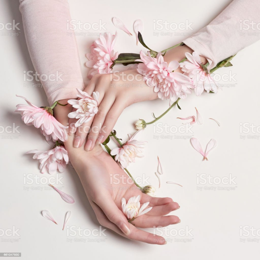 Fashion art portrait woman in summer dress and flowers in her hand with a bright contrasting makeup. Creative beauty photo girls sitting at table on a contrasting pink background with colored shadows stock photo