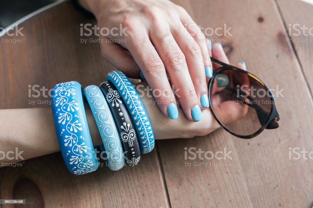 Fashion art with woman hands with blue menicure and blue boho style bracelets stock photo