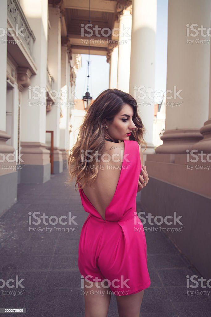 Fashion, attractive woman dressed in a sexy pink jumpsuit stock photo