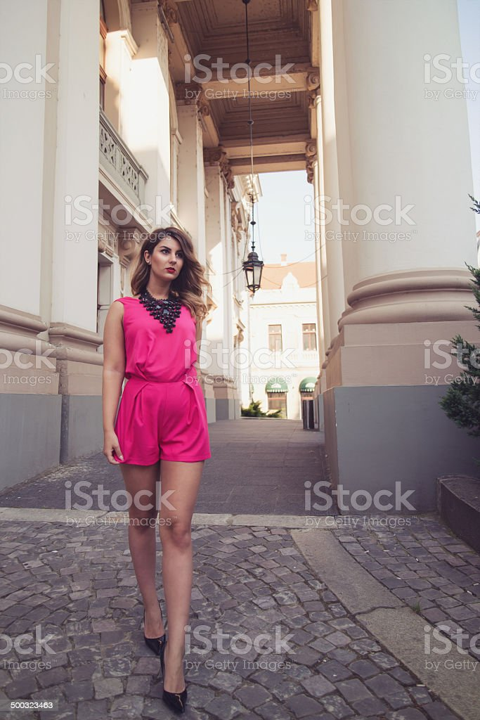 Fashion, attractive woman dressed in a sexy pink jumpsuit walking stock photo