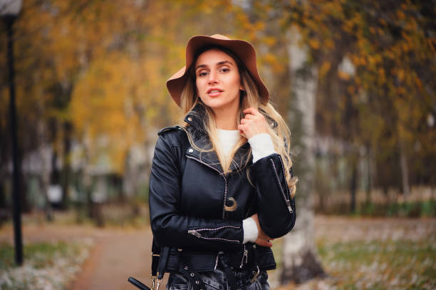fashion autumn portrait of young happy woman walking outdoor in fall park in hat and leather jacket stock photo