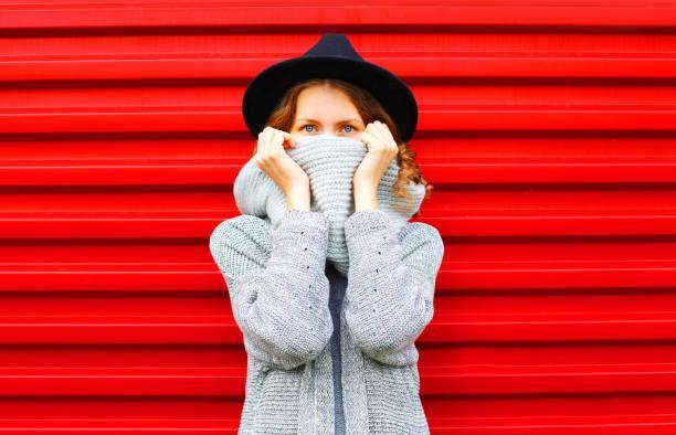 mode herbst porträt frau verbirgt ihr gesicht halstuch auf rotem grund - mützenschal stock-fotos und bilder