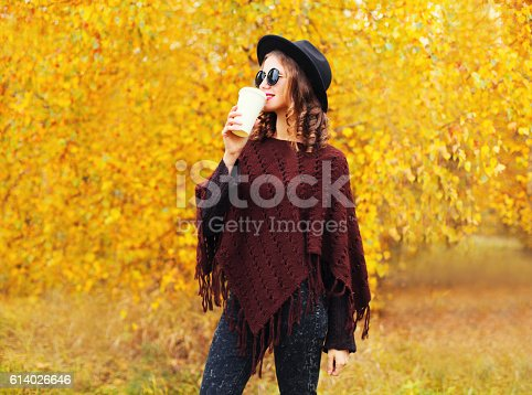 469211680 istock photo Fashion autumn woman with coffee cup, black hat sunglasses poncho 614026646