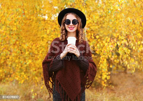 469211680 istock photo Fashion autumn woman with coffee cup wearing black hat poncho 614028932