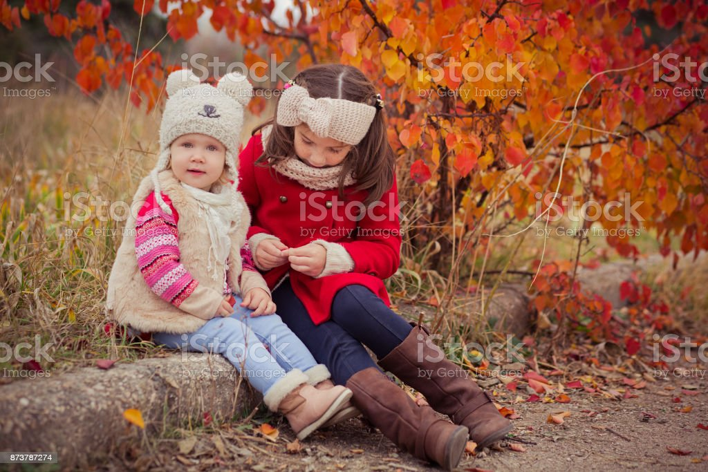 Fashion baby girls sisters stylish dressed brunnette and blond wearing warm autumn clothes jackets posing happy together in colourful forest foliage.Face with freckling stock photo