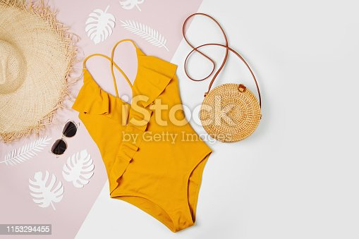 Fashion bamboo bag and sunglass, straw hat and swimsuit. Flat lay, top view. Summer Vacation concept.