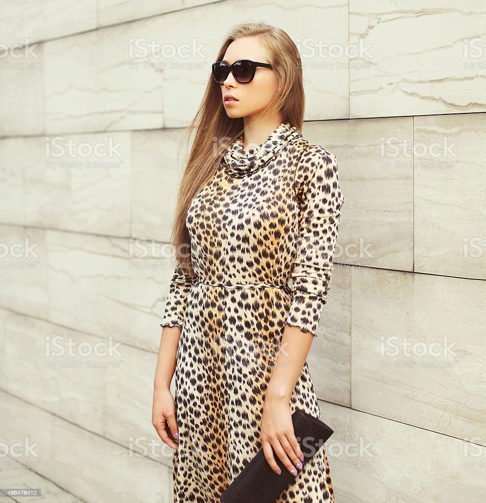 Fashion beautiful blonde woman wearing a leopard dress and sungl stock photo